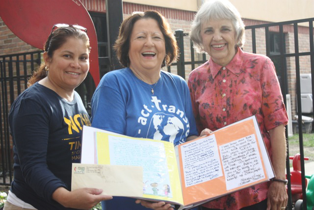 United Methodist Women share their book of letters to Publix along with CIW member Nely Rodriguez