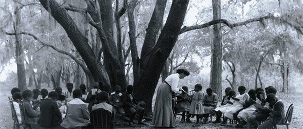 Early teachers at the Penn Center education a group of school-age children under the school ground's ancient oaks.