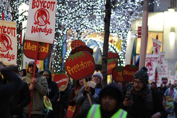 Marchers pass Rockefeller Center along 5th Avenue on their way to the offices of Wendy's Board Chairman Nelson Peltz.